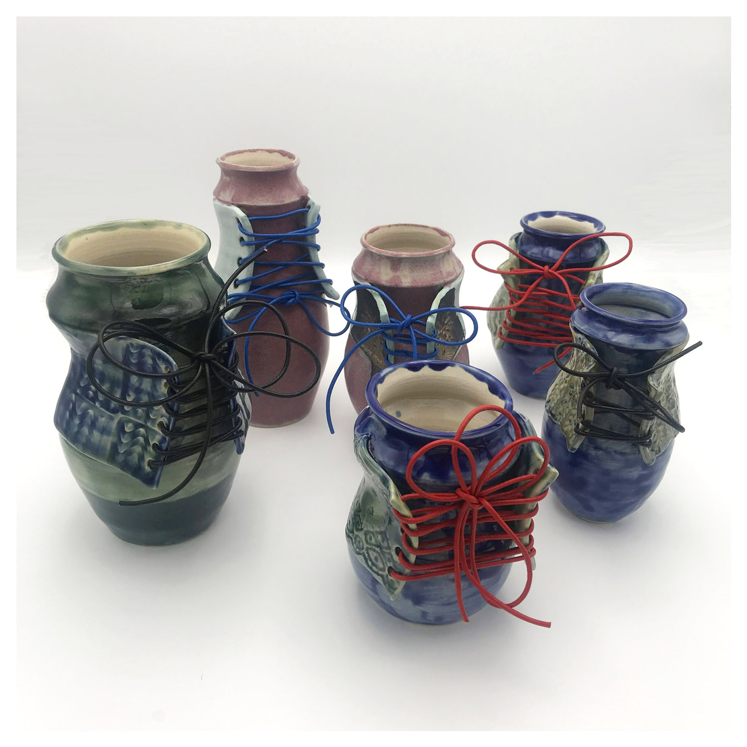 Nicole Lyster Sassy Lady Bottles Stoneware Ceramic up to 200mm high up to £60 Green Blue and Pink Glazed Vases with Spanish Lace Bodice and Leather Laces Suitable for Flowers or Storing Items.